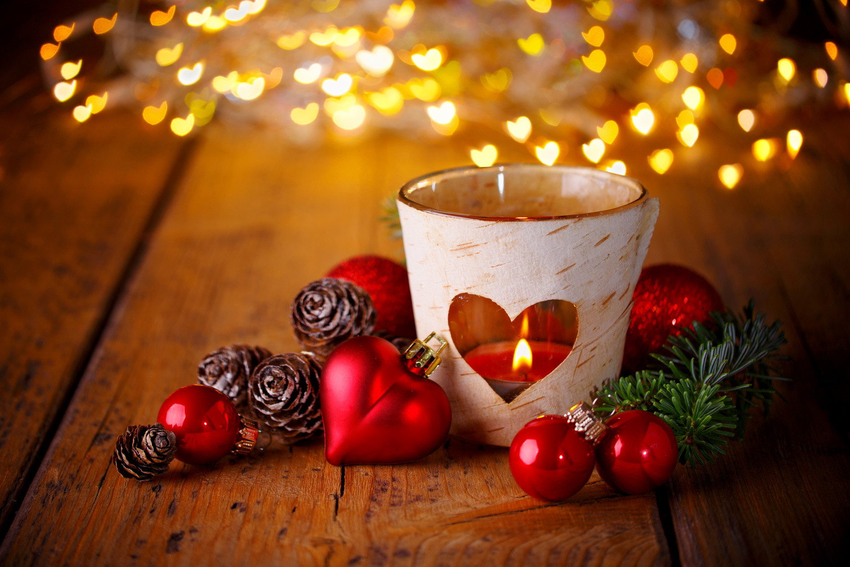 Christmas background -- Decoration with burning candle and heart shaped lights on wood