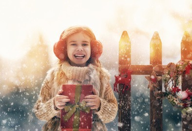 Happy child girl with Christmas gift on a winter walk in nature